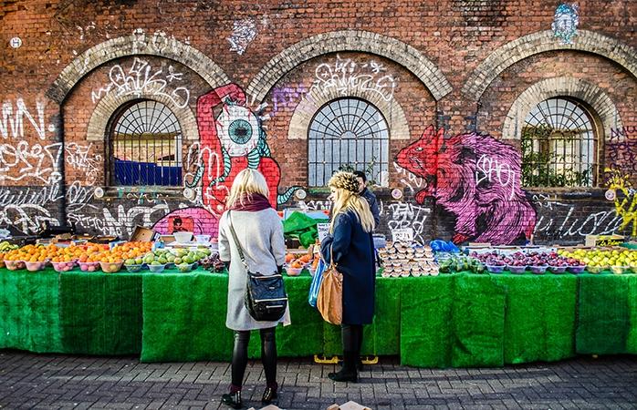 Două fete lângă un stand cu fructe la Brick Lane, Estul Londrei.