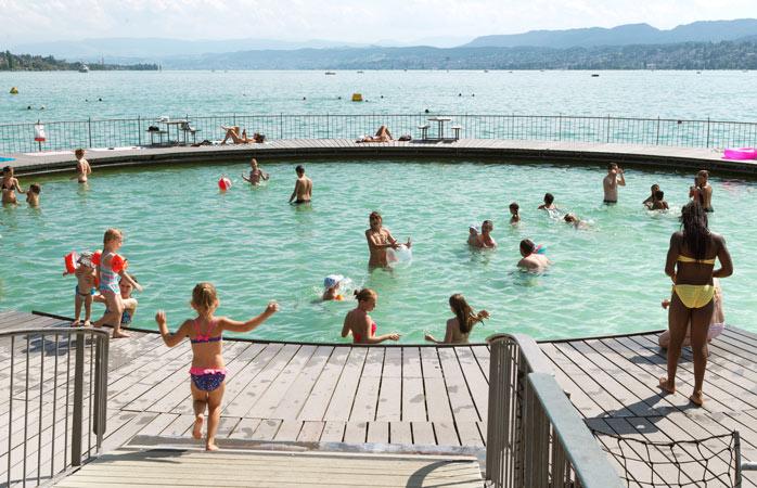 Iată cum, o simplă construcție circulară de lemn plasată strategic la malul unui lac, poate schimba cursul unei zile de vară obișnuite din Zurich