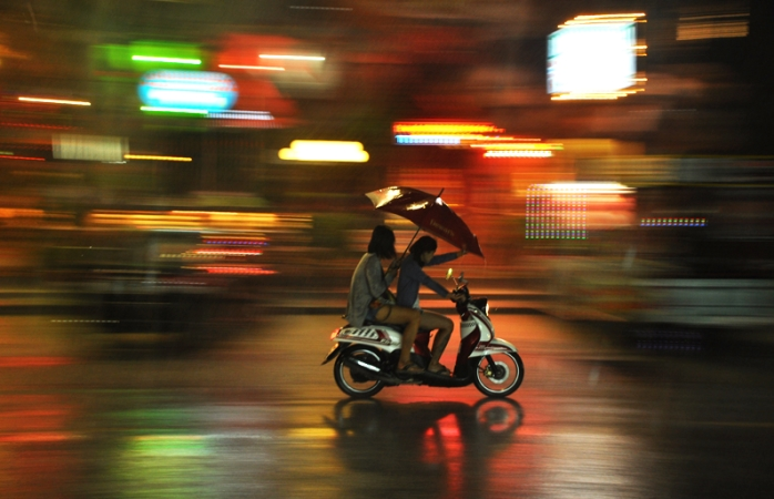 Un cuplu pe scuter apărându-se de ploaie cu o umbrelă.