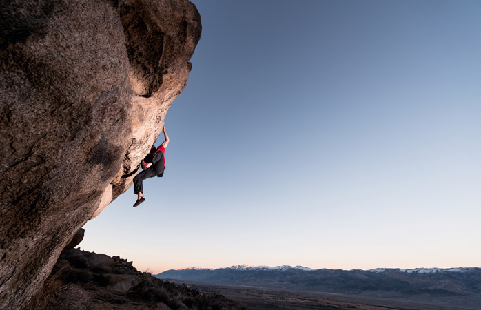 Un alpinist ce se sprijină de un bolovan abrupt din sudul Californiei (și pentru care sperăm că are asigurare)