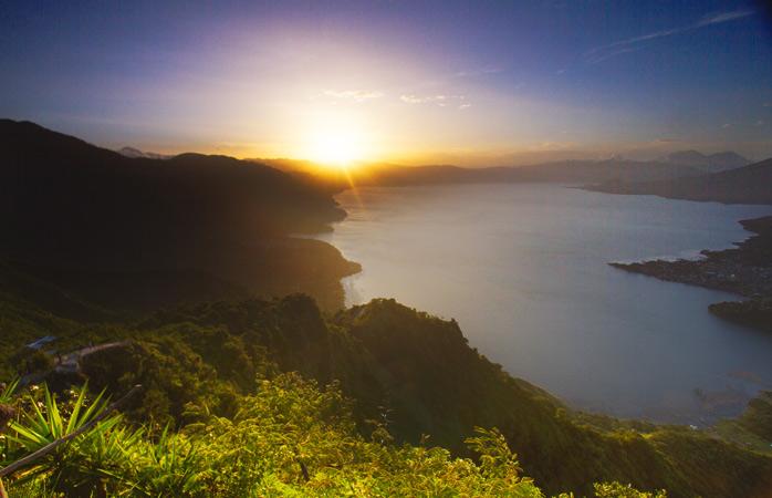 Wake up to the rays shining over Lake Atitlan in Guatemala