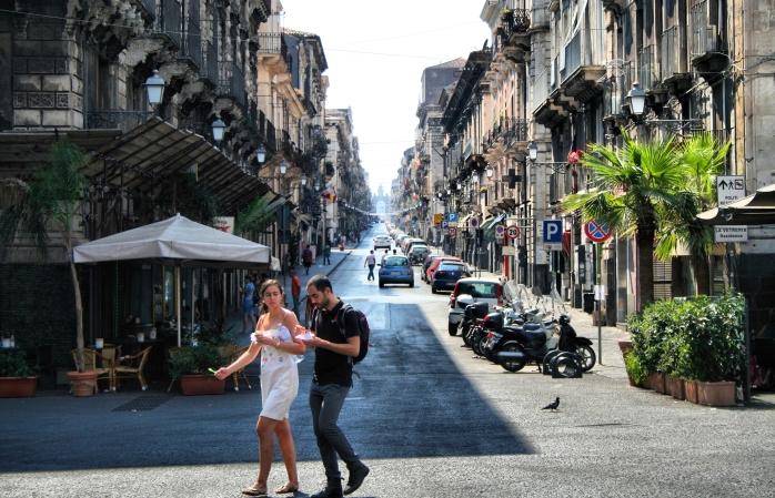Un cuplu ce ia prânzul, traversând strada în Catania
