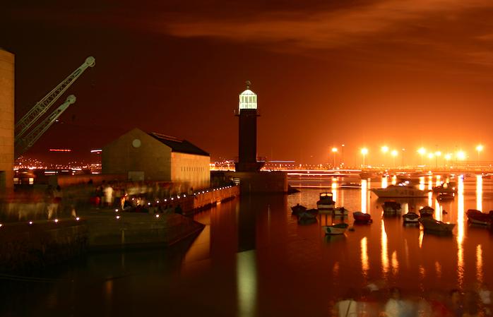 O seară de vară în Vigo, cu umbrele oamenilor savurând o ședere plăcută în port.