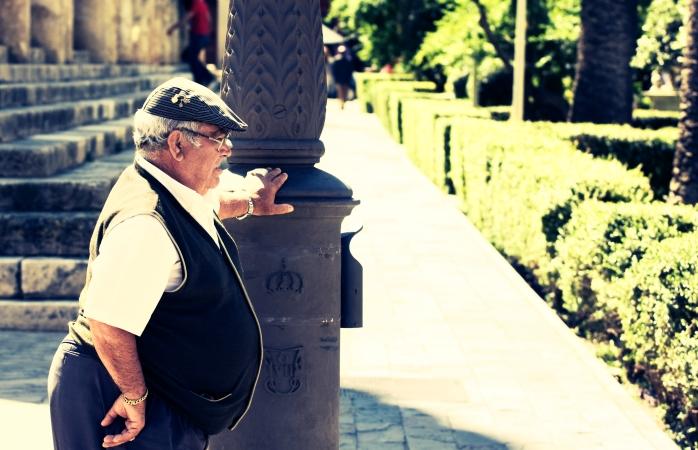 Un om în vârstă din Sevilla, sprijinindu-se de un stâlp într-o zi fierbinte de vară.
