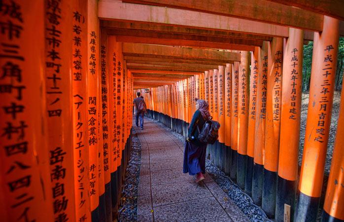 """Porțile tradiționale japoneze cunoscute drept """"torii"""" conduc către Altarul Fushimi Inari"""
