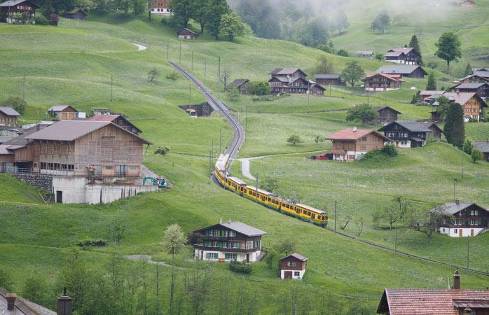 Încearcă să ajungi în vârful dealului în timp ce trenul se pierde la vale în urma ta, în peisajul netulburat de sat alpin - Griendelwald