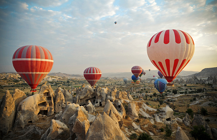 Baloanele colorate cu aer cald se înalță deasupra Cappadociei de parcă își iau o vacanță de la viața pe acest Pământ