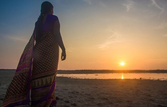 O femeie împreună cu sari-ul ei privesc răsăritul