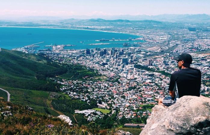 Un bărbat care admiră priveliștea coastei din Cape Town.