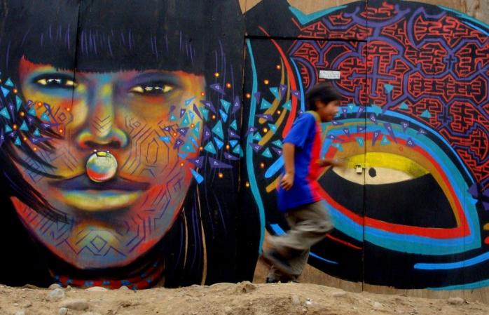 Un băiat alergând pe lângă desenele cu graffiti de pe zidurile din Lima