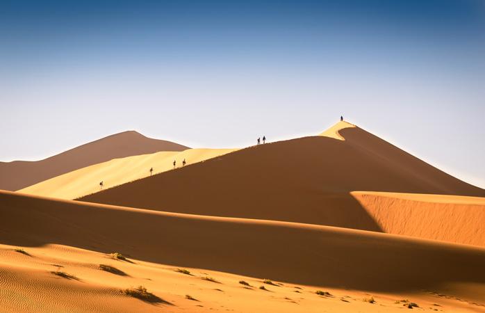 Drumeții călare pe dunele ce par întinse până la capătul pământului
