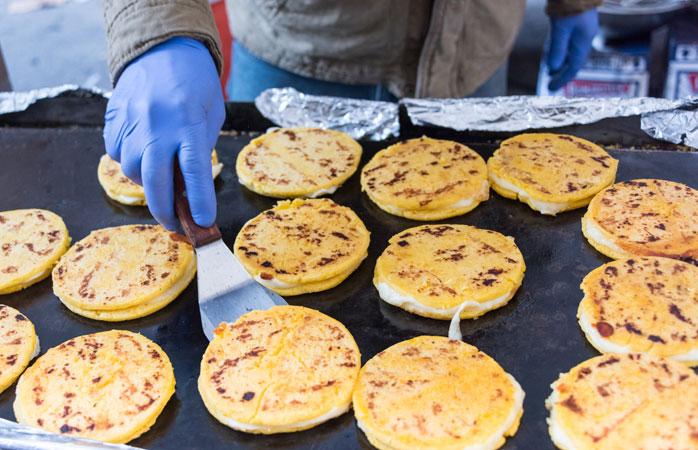 Arepas proaspete cu brânză se pregătesc de zor pe grătarele columbiene